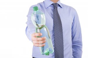 Businessman offering a green bottle.