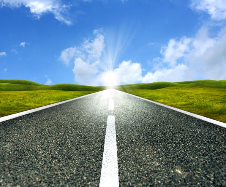 Empty asphalt road towards bright sun