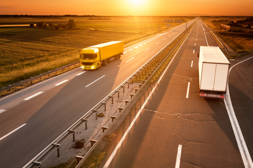 Yellow and white truck in motion blur on the highway at sunset