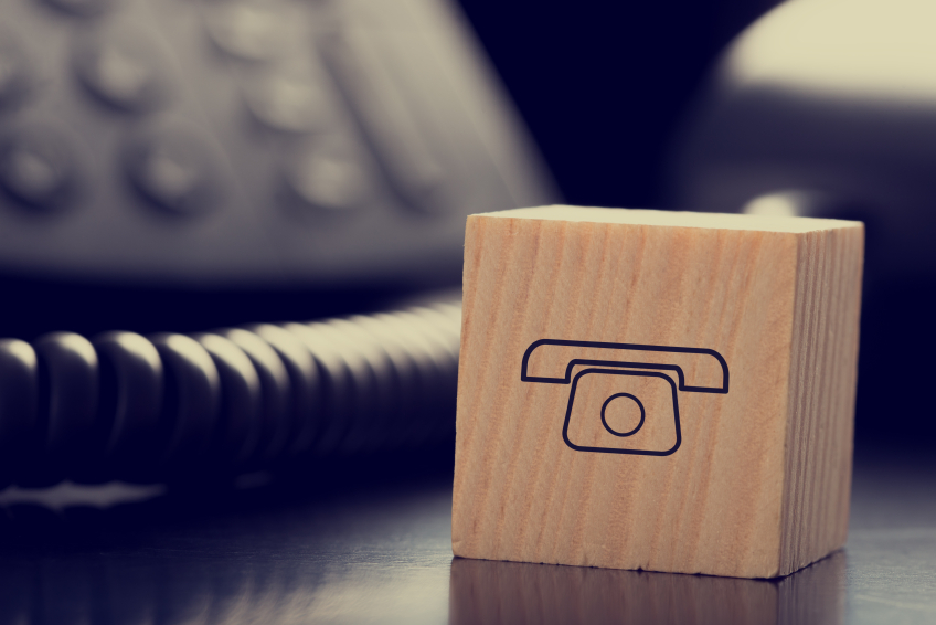 Retro Image of Wooden Block with Graphic of Old Fashioned Telephone in front of Other Black Telephone.