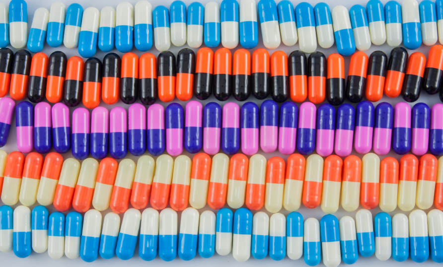 variety of pill capsules on white background, colorful