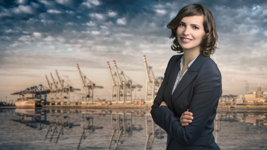 Attractive businesswoman with curly brown hair wearing a stylish jacket standing in front of a harbor or business port view smiling at the camera, upper body portrait