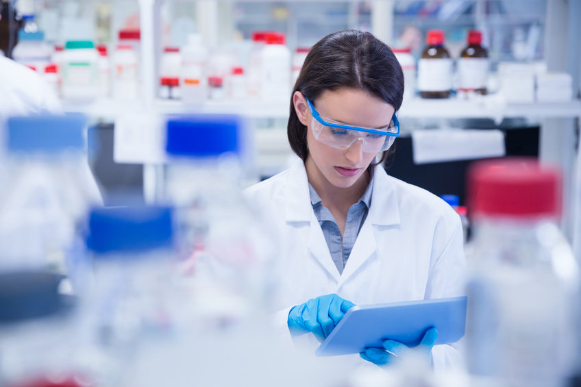 Chemist wearing safety glasses and using tablet pc in lab