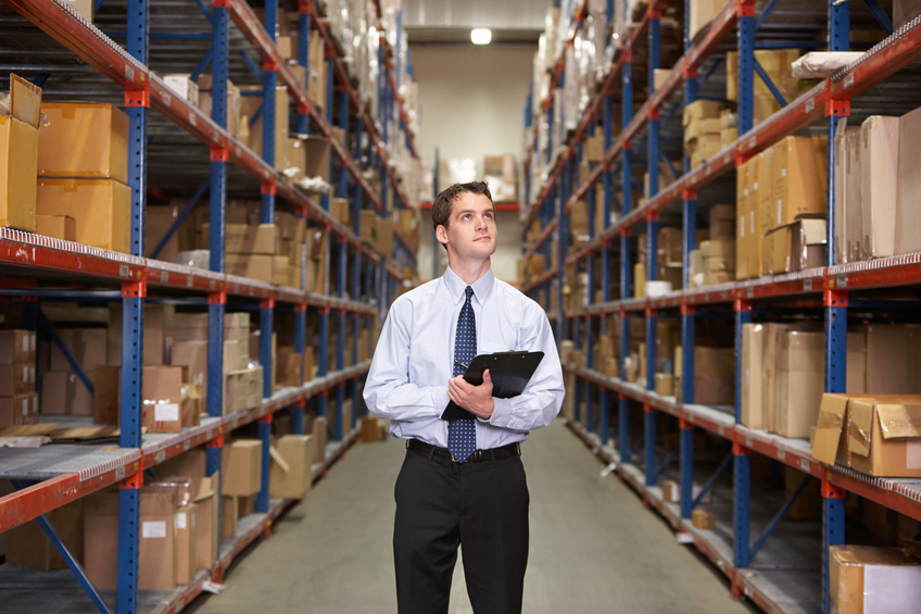 Manager In Warehouse With Clipboard Looking Up At Boxes