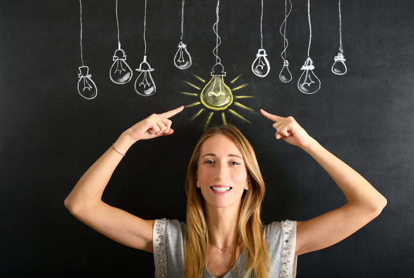 Young businesswoman pointing a big glowing light bulb sketched on blackboard